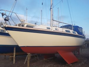 white sailboat with red hull after renovations